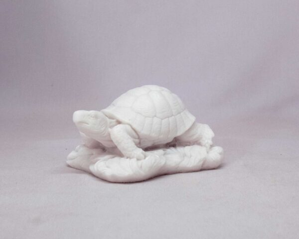 The statue of a turtle moving on sand in White color