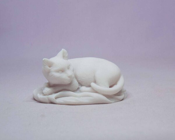 The statue of a cat sleeping on a pillow in White color
