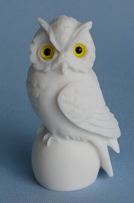 Owl sitting on a sphere in White color looking left