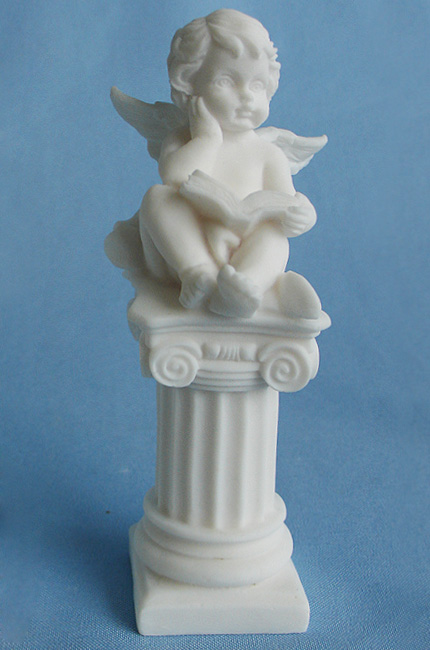 A statue of an Angel sitting on a column in White color