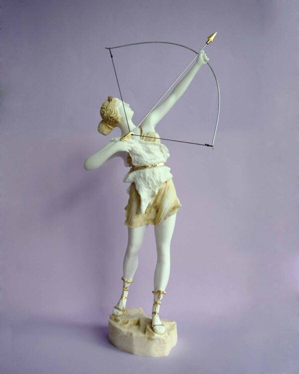 The statue of Greek Goddess Artemis hunting, ready to shoot with bow in Patina color