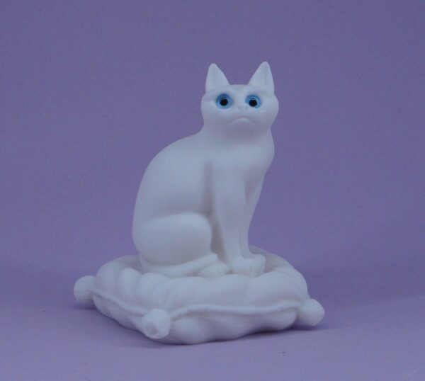 The statue of a cat sitting on a pillow in White color