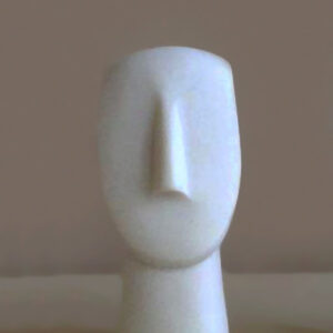 A statue of a face in Cycladic art type 2 in White color