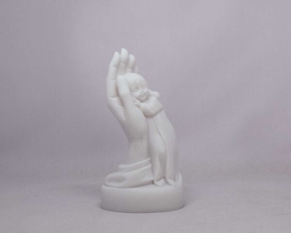 The statue of a girl is held by a hand in White color