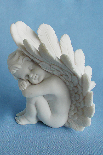A statue of an Angel used for bookend at left side in White color
