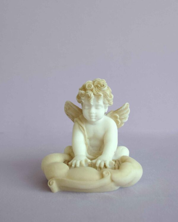 A statue of an Angel playing the piano in Patina color