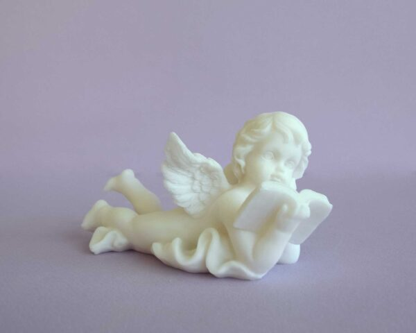 The statue of an Angel lying down reads the Bible in White color