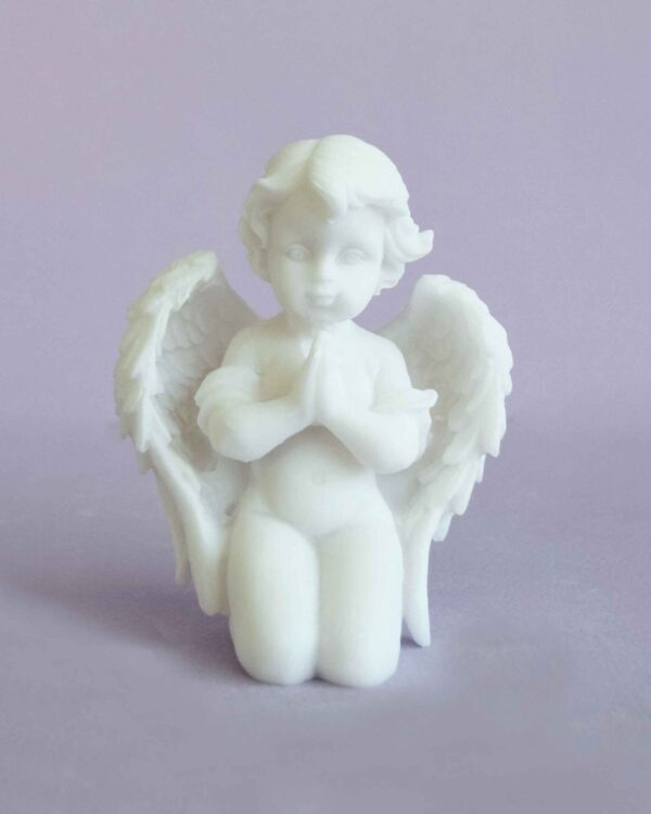 The statue of an Angel praying on its knees in White color
