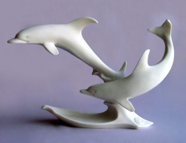 The statue of two dolphins swimming in White color