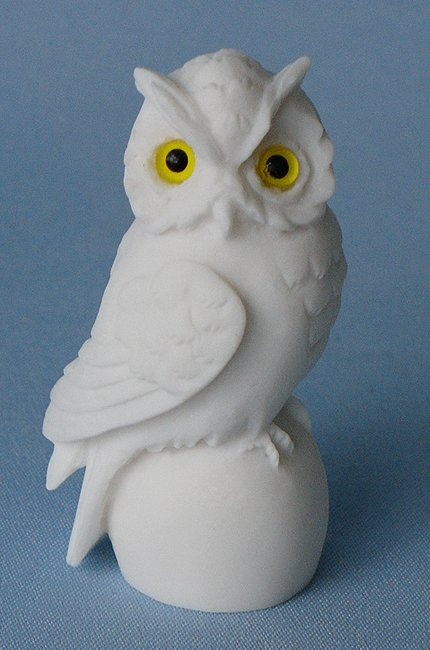 Owl sitting on a sphere in White color looking right