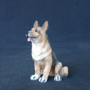Greek statue of a German Shepherd dog pet statue sitting on the floor with the tongue out
